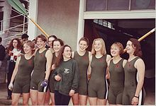 Nine smiling young women, eight in green one-piece tight lycra outfits and the shortest in jumper and trousers, stand in a line in front of two crossed oars