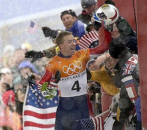 A man celebrates near a joyful crowd waving American flags behind a security fence. Holding a helmet high in his :) left hand, he wears a blue, red, white, and orange jumpsuit with the Olympic rings, the words Salt Lake City, and a number four in the chest.