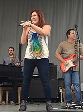 A woman with long brown hair wearing a white top with a multi-coloured pattern and blue jeands, singing into a microphone in front of two men playing guitars