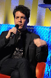 Joe Henry sitting on a sofa in a suit and talking to a microphone in his right hand.