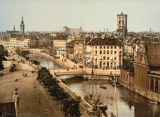 Slotsholmen canal, as seen from the Borsen building (c. 1900). In the background from left to right: Church of the Holy Ghost, Trinitatis Complex, St. Nicholas Church and Holmen Church. KBH 1890-1900.jpg