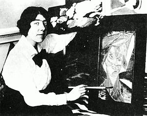 Kate Lechmere - Kate Lechmere pretending to finish her already framed painting Buntem Vogel (Colourful Bird) for the benefit of a press photographer, Rebel Art Centre, 1914.