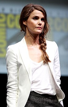 A young woman in a white top looks at the camera. Behind her is a wall with white and yellow logos.