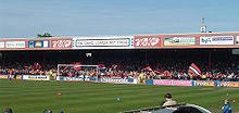 One of the stands of the Bootham Crescent association football ground, with supporters waving flags and a grass field below