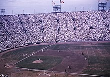 A baseball game being played in a stadium with high stands, seen from the right field side. The United States and Los Angeles flags are flying above the left field foul line, which is shorter than usual