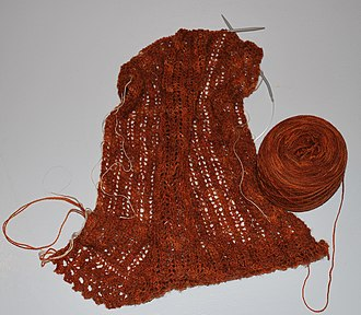 """Lace knitting - Rectangular lace shawl on the needles. White threads (""""lifelines"""") are strung through the pattern every twenty rows and will be removed upon completion."""