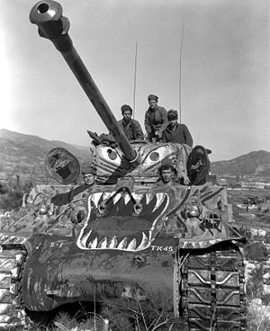 Operation Courageous - US soldiers prepare to advance along the Han River area, Korea, in their M4A3E8 Sherman tank (painted with a tiger scheme as a psychological effort to undermine Chinese morale), during offensive launched by the 5th RCT against the Chinese forces in that area.