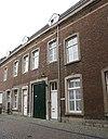 foto van Huis waarvan de lijstgevel een geheel vormt met die van het nr 2. Nr 6 met koetspoort en een garageingang