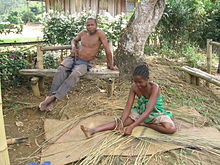 A Malagasy girls sits on the ground weaving with reeds, while an older gentleman sits on a bench above her.