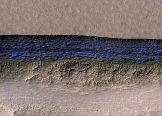 A cross-section of underground water ice is exposed at the steep slope that appears bright blue in this enhanced-color view from the MRO. The scene is about 500 meters wide. The scarp drops about 128 meters from the level ground. The ice sheets extend from just below the surface to a depth of 100 meters or more. Mars exposed subsurface ice.jpg