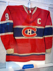 "A red sweater with a blue band and white trim across the middle. There is a stylized ""CH"" logo across the middle, the letter ""C"" at the left breast and the number 9 on the arms."