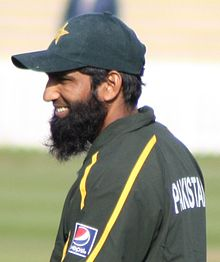 The head and shoulders shot of a beard man, wearing a dark green cricket cap and shirt.