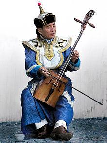 Violonist în costum tradițional mongol predominant albastru, ținând în mâini un viol de lemn cu două corzi, al cărui gât se termină în formă de cap de cal.
