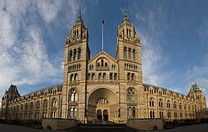 The Natural History Museum, shown in wide-angle view here, has an ornate terracotta facade typical of high Victorian architecture. The carvings represent the past and present diversity of nature.