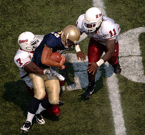 Tackle (football move) - College football game: Navy quarterback Kaipo-Noa Kaheaku-Enhada (blue) is tackled by Massachusetts defensive back James Ihedigbo, (white 7), and linebacker Charles Walker, (white 11).