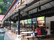 A row of food stalls and picnic tables, with an awning above.