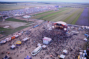 Music festival in Nickelsdorf, Austria, picturing both the main stage and the camping grounds on the farm behind.