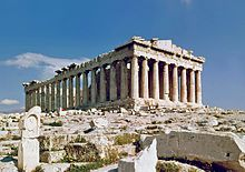 The Parthenon is a rectangular building of white marble with eight columns supporting a pediment at the front, and a long line of columns visible at the side