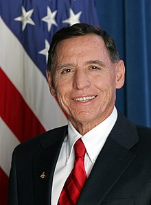 "Head and shoulders of a man in his forties with close-cropped dark hair, dressed in a dark blue suit, a white shirt and a red striped tie. On his right lapel is the President's ""Call to Service"" Award medal. Over his right shoulder the U.S. flag."