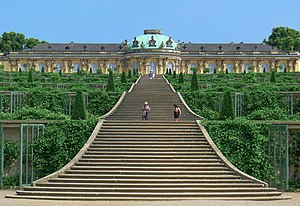 Sanssouci - The south facing garden façade.  Frederick the Great ignored his architect's advice to place the piano nobile upon a low ground floor. As a result, the palace failed to take maximum advantage of its location. Its windows are devoid of views, and seen from its lower terraces it appears to be more of an orangery than a palace.