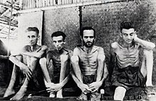Four malnourished shirtless men sit against a wall