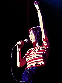Самка певица Патти Смит, пение в микрофон на сцене производительности.  Она держит микрофон с одной стороны;  другой поднимается вверх и в закрытой руке.