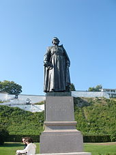 A gray steel statue of Père Jacques Marquette, atop a marble pedestal