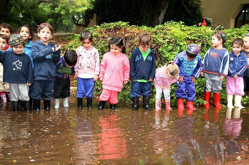 ילדי קיבוץ עלומים בשלולית גשם