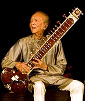 An elderly man is seated at the centre of the image, holding a sitar.
