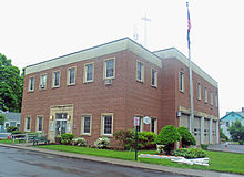 "A roughly cubical two-story brick and concrete building with metal lettering spelling out ""Village of Rhinbeck"" above the entrance. On the left side are four garage doors and a flagpole from which an American flag hangs."