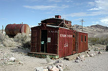 "An abandoned wooden rail car rests on a bed of gravel. A large, rusting, cylindrical tank is nearby, among low bushes. Barren, striated hills can be seen in the distance. Lettering on the car says, ""L.A. & SL"" and ""Union Pacific"". A sign on the end of the car says, ""Danger: Do Not Enter"" and ""Peligro: No Entre"