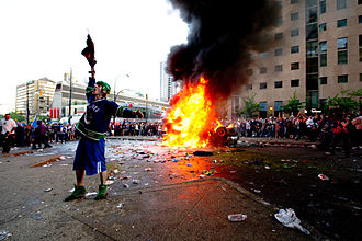 2011 Vancouver Stanley Cup riot - A rioter cheers on while a car burns surrounded by a large crowd