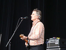 Forster is shown in upper half, left profile. He is standing, singing into a microphone and playing an electric guitar. Some musical equipment is visible behind him. His shirt is light coloured and he wears dark pants.