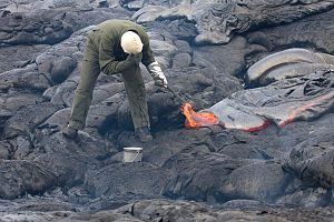 Volcanology - A volcanologist sampling lava using a rock hammer and a bucket of water