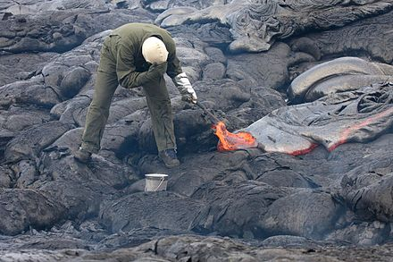 A volcanologist sampling lava using a rock hammer and a bucket of water Sampling lava with hammer and bucket.jpg