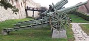 a pale green-painted wheeled artillery piece on a concrete plinth