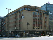 "A 1950s or 1960s six-story building, predominantly made of yellow brick with red brick used around the windows. Other ornamentation include a large round black and white clock, a large black cross symbol, and ""Scientology Kirche Hamburg e.V."" lettering."