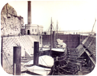 A photograph with two steamships resting in a dewatered drydock with a building housing the engine for operating the lock's gates in the background