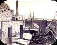 Uma fotografia com dois navios a vapor descansando em um dique seco desidratado com um edifício que abriga o motor para operar portões da fechadura no fundo