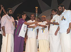 Smt. K.M Beenamol, Padma Shri & Rajiv Gandhi Khel Ratna Awardee hands over the Queen's Baton 2010 Delhi to the Chief Minister of Kerala, Shri V.S. Achuthanandan in the presence of Sports and Youth Affairs Minister, Kerala.jpg