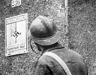 Phoney War - A French soldier examines a German street sign during the Saar Offensive