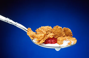 A spoon containing breakfast cereal flakes, pa...