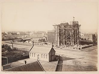 St Patrick's Cathedral, Melbourne - Photograph of St Patrick's Cathedral with scaffolding at front and St Patrick's School, Eastern Hill, c. 1866