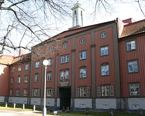 Landshövdingehus - Kvarteret Standaret, designed by Arvid Fuhre, built in 1922–1923 at Karl Johans torg is a classic example of national romanticism in the form of a landshövdingehus. The buildings are arranged around a central axis. Note the relation between the materials – the wooden panel covering the stone base and the distinct vertical elements.Arvid Fuhre was also the main architect of the buildings in Gothenburg 300 Years foundation Jubilee exhibition 1923 at the Liseberg,today an amusement park. The design and colour scheme of Standaret and Liseberg have great similarities. Standaret is now protected as a building of cultural significance by the city of Gothenburg.