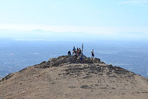 "Mission Peak - The summit of Mission Peak with the San Francisco Peninsula in the background, the Sutro Tower directly above the iconic summit marker nicknamed ""Mission Peeker"" and Mount Tamalpais at the upper right"