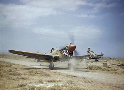 1943: A Kittyhawk Mark III of 112 Squadron, taxiing through scrub at Medenine, Tunisia. The ground crewman on the wing is directing the pilot, whose view ahead is hindered by the aircraft's nose. TR 000978 kittyhawk.jpg