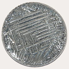 A shiny silver-white medallion with a striated surface, irregular around the outside, with a square spiral-like pattern in the middle.