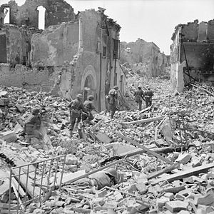 Northamptonshire Regiment - Troops of the 5th (Huntingdonshire) Battalion, 11th Infantry Brigade, 78th Infantry Division pick their way through the ruins of Argenta, 18 April 1945.
