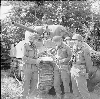 East Riding of Yorkshire Yeomanry - Major W Holtby, commanding 'C' Squadron, East Riding Yeomanry, 27th Armoured Brigade, briefs troop commanders in front of his HQ Sherman tank, 28 June 1944.