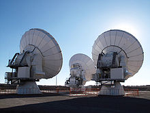 Three large parabolic-dish telescopes, seen from behind